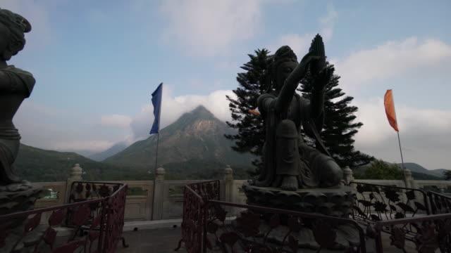 trucking shot, tian tan buddha in mountain range - tian tan buddha stock videos and b-roll footage