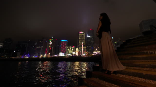 trucking shot, woman admires hong kong at night - evening gown stock videos & royalty-free footage