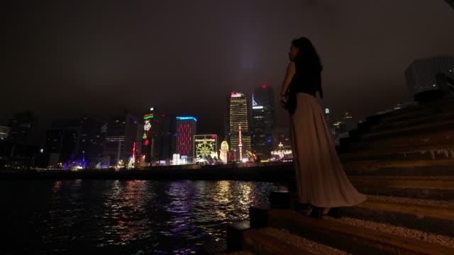 Trucking shot, woman admires Hong Kong at night