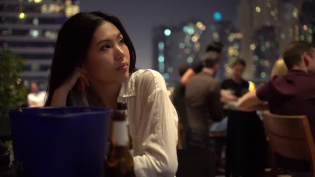 trucking shot, woman waits at restaurant table in dubai - バッグ点の映像素材/bロール