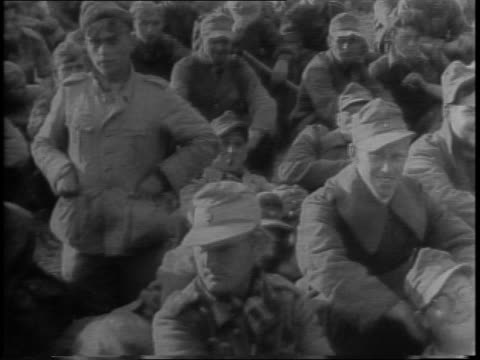 Truckload of German prisoners past camera also on motorcycle / captured officers / mass of prisoners seated / Adolf Hitler superimposed over smiling...