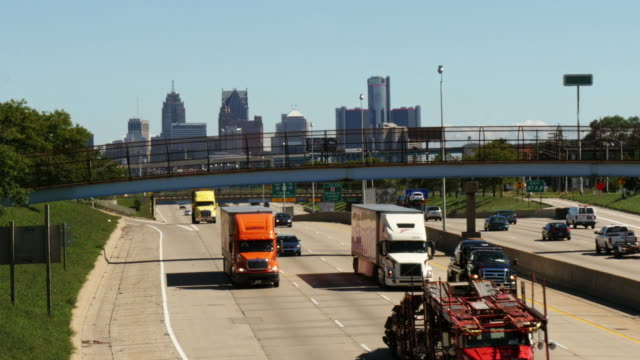 trucks and cars dringing on freeway with overpass in detroit. downtown in background. - aerial stock videos & royalty-free footage