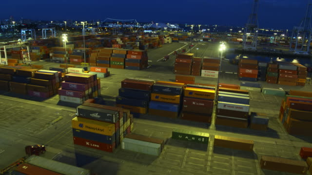 vidéos et rushes de trucks and pickups driving between shipping containers in port of long beach at night - aerial - groupe d'objets
