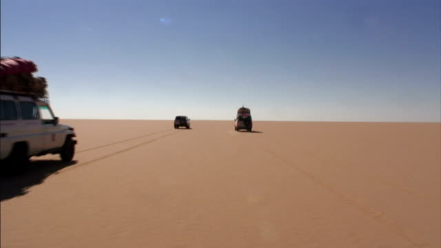 vidéos et rushes de trucks are parked in the sand of a vast desert. - paysage enchanteur