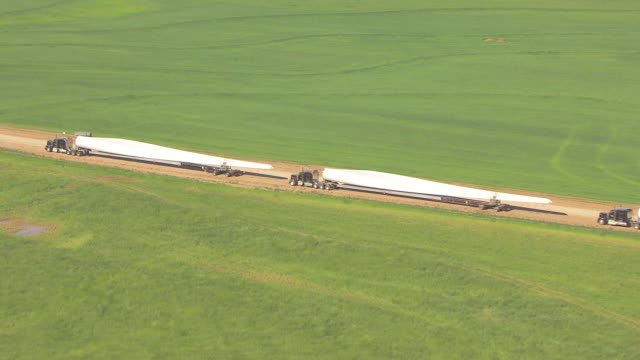ws aerial zi trucks carrying large blades for new wind turbine generators at flat ridge wind farm in harper county / kansas, united states - trucks in a row stock videos & royalty-free footage