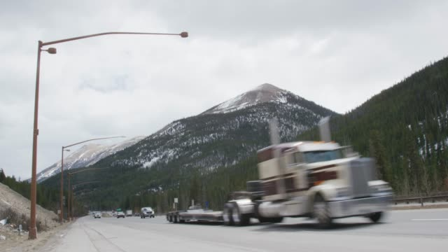 trucks, cars, and other vehicles drive along interstate 70 in the rocky mountains of colorado in winter - road sign stock videos & royalty-free footage