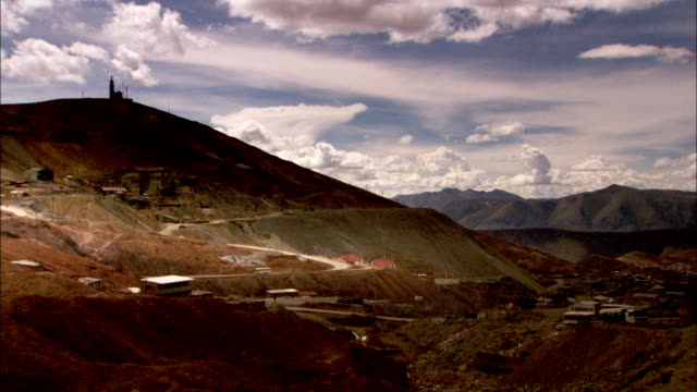 Trucks drive along winding roads past a silver mine. Available in HD.