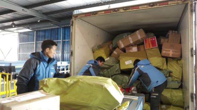 trucks drive away from a zto express inc sorting facility in shanghai china on friday feb 10 a worker sorts boxes on a conveyor workers inspect boxes... - post stock-videos und b-roll-filmmaterial