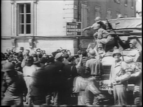 stockvideo's en b-roll-footage met us trucks drive down street / liberated french civilians tear down nazi propaganda posters lining the streets / allied military patrol the streets... - geallieerde mogendheden