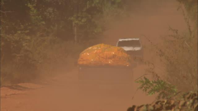 vídeos de stock, filmes e b-roll de trucks drive on a dusty dirt road. - estrada rural
