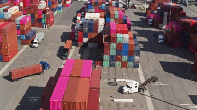 trucks driving through container terminal - aerial - long beach california stock videos & royalty-free footage
