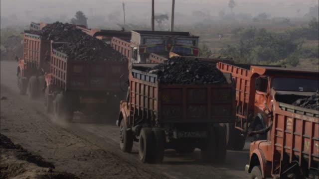 vídeos de stock, filmes e b-roll de trucks hauling coal drive along a dirt road at a construction site. - mineral