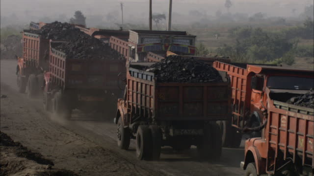 vidéos et rushes de trucks hauling coal drive along a dirt road at a construction site. - charbon