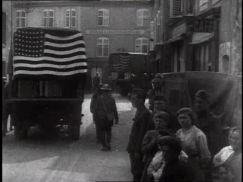 trucks loaded with coffins driving away american flags draped on the back and soldiers marching next to them / germany - 1918 stock videos and b-roll footage