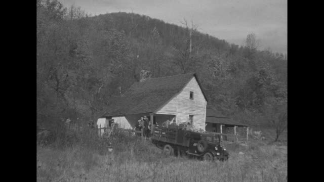 trucks moving down dirt road to shack mountains in bg / truck backed up to house as men load up truck with household goods / men walking down path... - civilian conservation corps video stock e b–roll