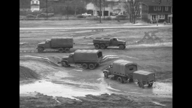 vidéos et rushes de trucks, newly assembled at general motors factory, being driven on track past camera / trucks being driven through mud on testing ground / truck... - essai de voiture
