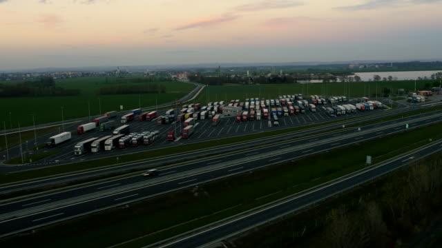 vídeos de stock e filmes b-roll de estrada de camiões aérea em um parque de estacionamento local - posto de gasolina