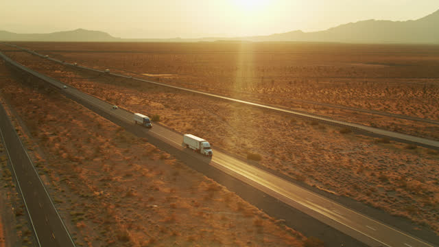 vídeos de stock e filmes b-roll de trucks on freeway crossing desert - aerial - anoitecer