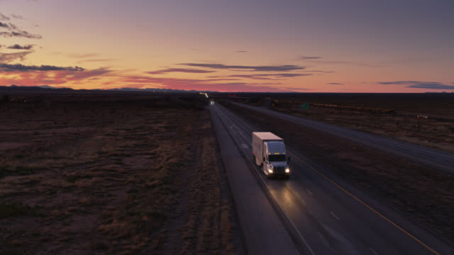 trucks on i-10 in new mexico desert at sunset passing aerial camera - american interstate stock videos & royalty-free footage