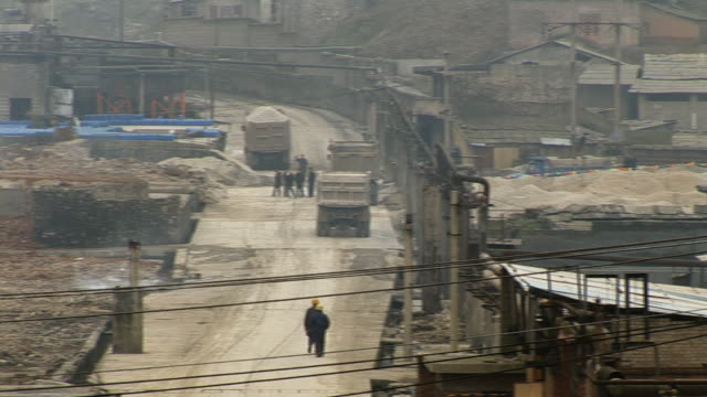 stockvideo's en b-roll-footage met ha ws trucks on road in phosphorous mine/ pan ws smoke coming from top of industrial building/ guiyang, china - documentairebeeld