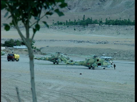trucks operate around military gunship helicopters tajikistan - ムラがある点の映像素材/bロール