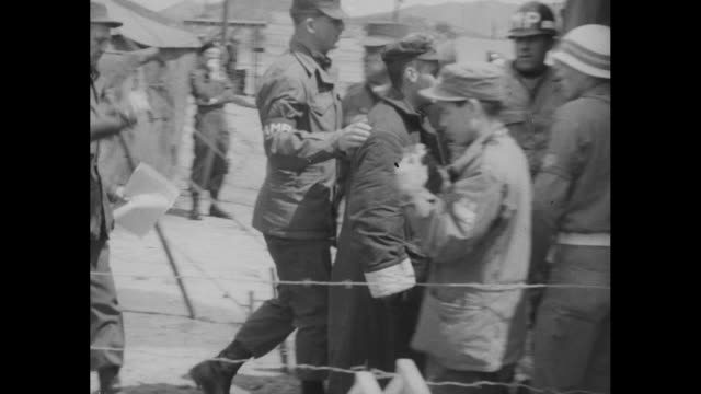 trucks parked in row at munsan south korea us soldiers standing around waiting / released us korean war pow gets out of truck soldier checks his name... - prisoner of war stock videos & royalty-free footage