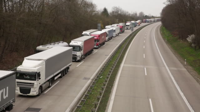 trucks queue on the a12 highway between berlin and the polish border in frankfurt oder. polish government closed the country's borders on saturday... - stau stock-videos und b-roll-filmmaterial