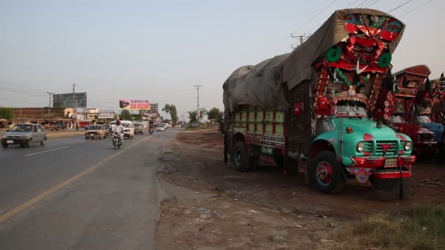 trucks sit parked along the roadside of national highway 5 in punjab pakistan on wednesday oct 5 traffic drives along national highway 5 in rawat... - punjab pakistan stock videos and b-roll footage
