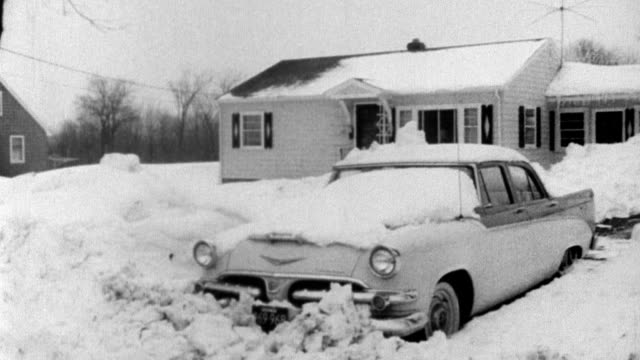 Trucks stalled on snow covered highway / cars buried in snow / men shoveling snow / stranded men sitting in restaurant women sleeping on benches /...