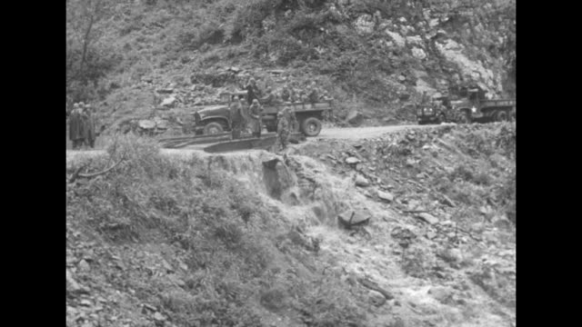 vidéos et rushes de trucks stopped on road as soldiers finish putting metal tracks over water running down hillside across road / closer view of soldiers as they finish... - actualités cinématographiques