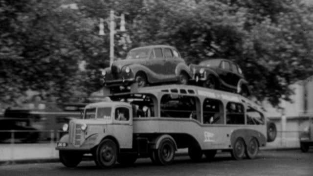 1952 B/W Trucks transporting cars on city street / United Kingdom