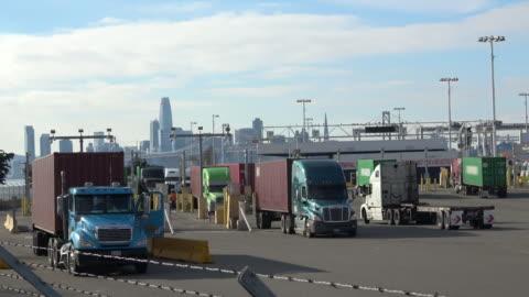 vidéos et rushes de camions de transport de cargaison de conteneurs du port - décharger
