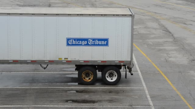 trucks with chicago tribune signage sit outside the chicago tribune printing facility in chicago, illinois, us, a truck backs into the loading dock... - トリビューンタワー点の映像素材/bロール