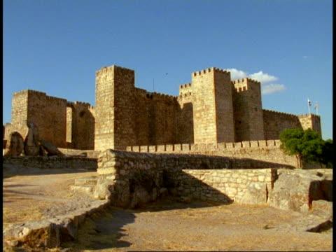 Trujillo Castle, Spain - WA castle against blue sky, cobbled street foreground