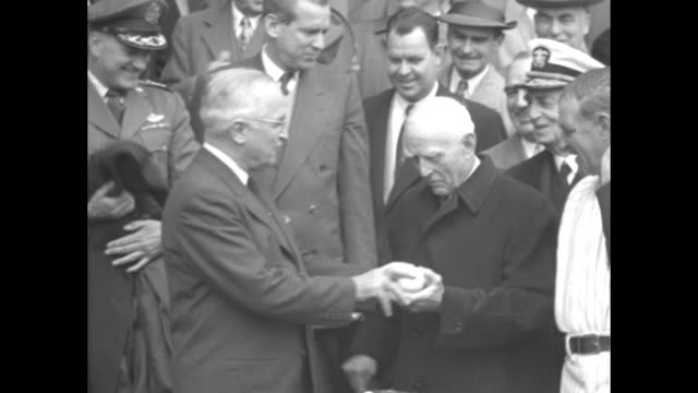 truman holding baseball and wearing baseball glove smiling playfully, other spectators nearby / truman in stands shaking hands with washington... - harry truman stock videos & royalty-free footage