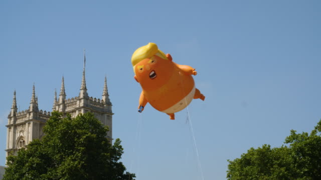 'trump baby' balloon flies over parliament square in protest during president trump's uk visit, london. - 飛行船点の映像素材/bロール