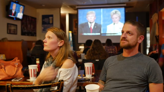 audience members at a debate watching party organized by the democratic party watch listen and react as hillary clinton and donald trump face off in... - election stock videos & royalty-free footage