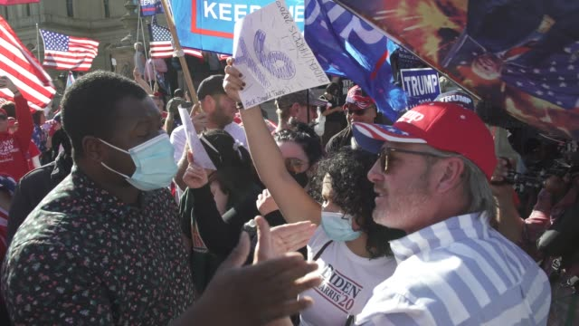 vidéos et rushes de trump supporters and biden supporters argue outside the michigan state capitol building after democratic candidate former vice president joe biden... - lansing