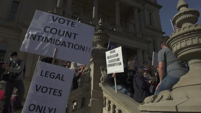 vidéos et rushes de trump supporters hold signs that claim there was election corruption at the michigan state capitol building after democratic candidate former vice... - lansing