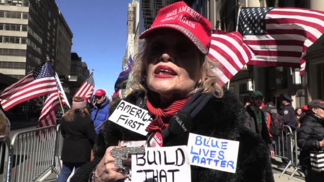 Trump supporters in MAGA hats flags and signs chant 'build the wall' 'Trump Trump Trump' in front of Trump Tower on 5th avenue