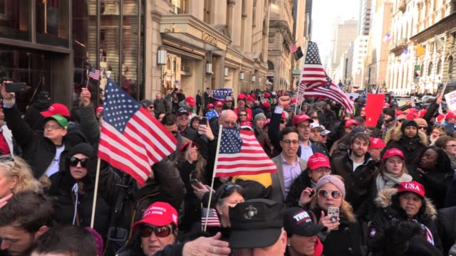 trump supporters in maga hats flags and signs chant 'build the wall' 'trump trump trump' in front of trump tower on 5th avenue - 詠唱点の映像素材/bロール