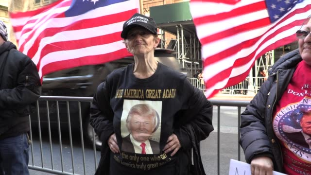 vídeos de stock e filmes b-roll de trump supporters in maga hats, flags and signs chant 'build the wall' 'trump trump trump' in front of trump tower on 5th avenue - partidário