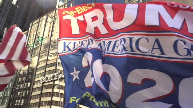 vídeos de stock e filmes b-roll de trump supporters in maga hats, flags in front of trump tower on 5th avenue. altercation when jovi val brings a confederate flag, argument ensues,... - partidário