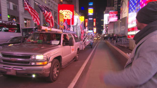Trump supporters SUV driving up to Times Square covered in American flags and stickers reading 'Trump Unity Bridge' also pulling a trailer with signs...