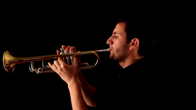 trumpet player against a black background - trumpet stock videos and b-roll footage