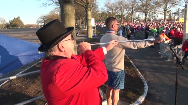 vidéos et rushes de trumpeter plays call to post to start marathon pan to runners - salmini