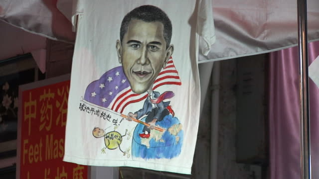 cu t-shirt with cartoon of barack obama walking on globe carrying american flag / yangshuo, guangxi, china - t shirt stock videos & royalty-free footage