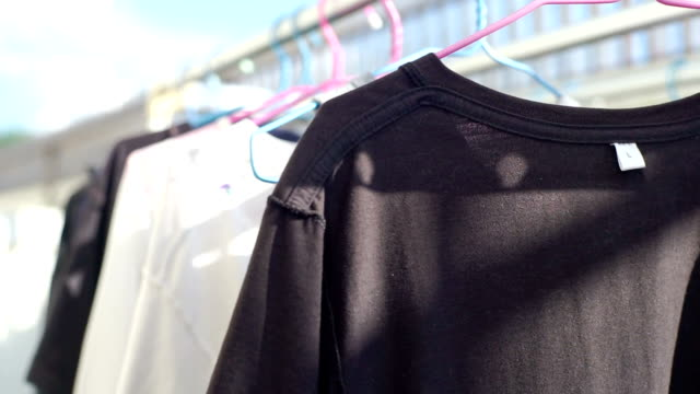 t-shirts hanging on a clothesline on daytime. - washing line stock videos and b-roll footage