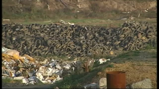 Kesennuma Waves lapping the shore PULL BACK to show tsunami rubble dumped along coastline at waste disposal and recycling site GV Huge waste disposal...