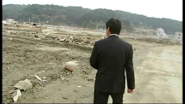 'Tsunami Revisited' A Town Abandoned Minamisanriku JAPAN Minamisanriku EXT Wreckage of car perched on top of damaged building ZOOM OUT to general...